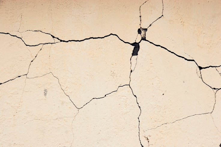 House painters filling a cracked wall